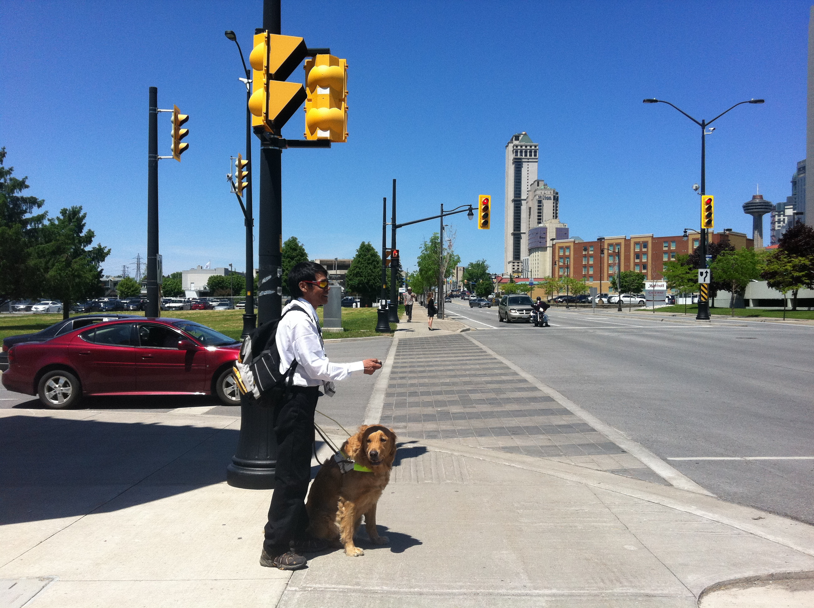 Picture of visually impaired pedestrian with guide dog using ta key2access fob to request crossing at an intersection
