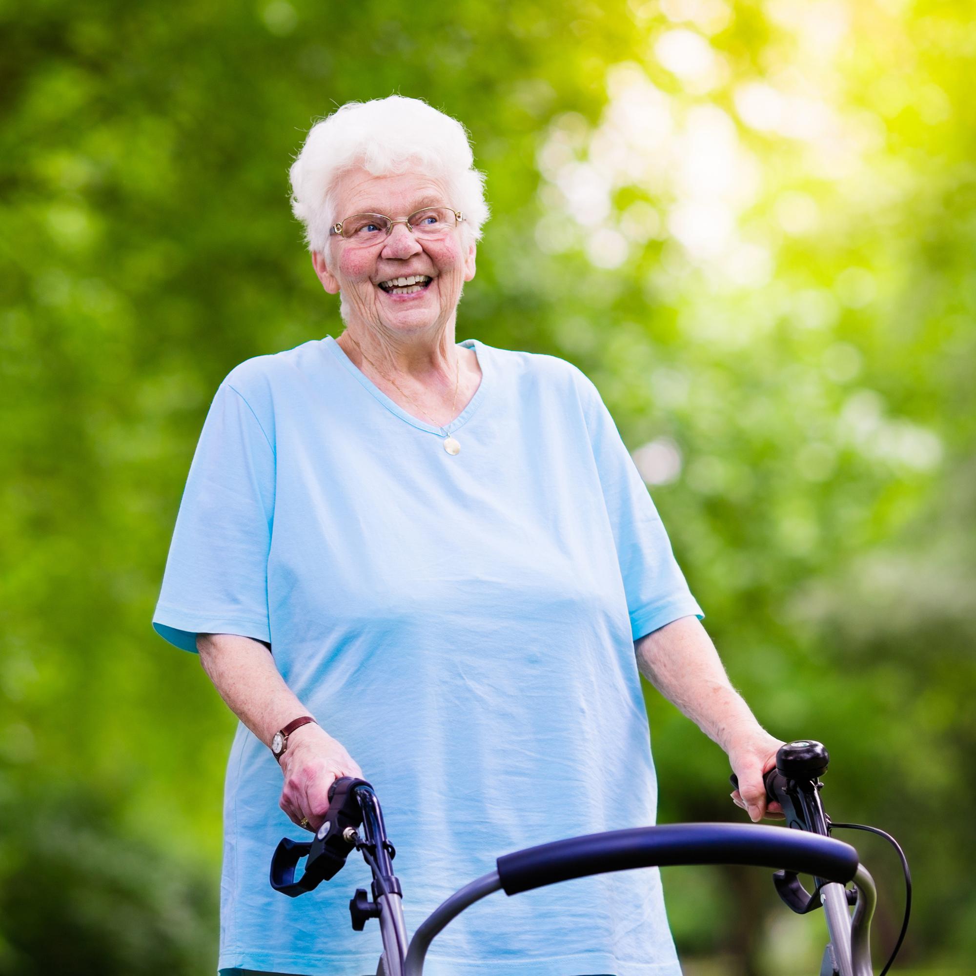 Elderly lady using a walker outside