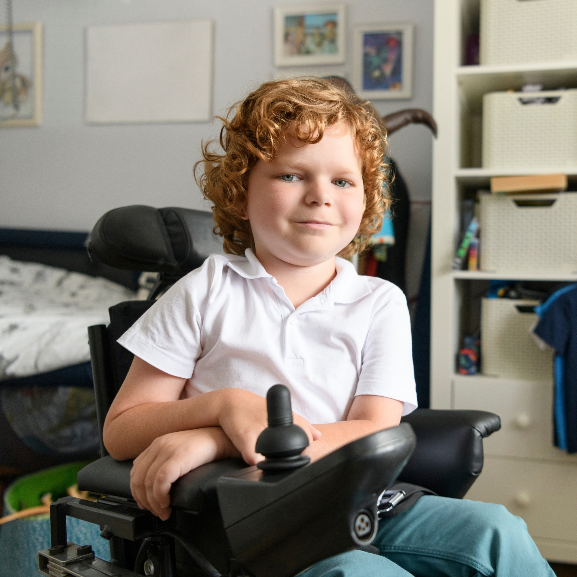 Young boy in power wheelchair at home