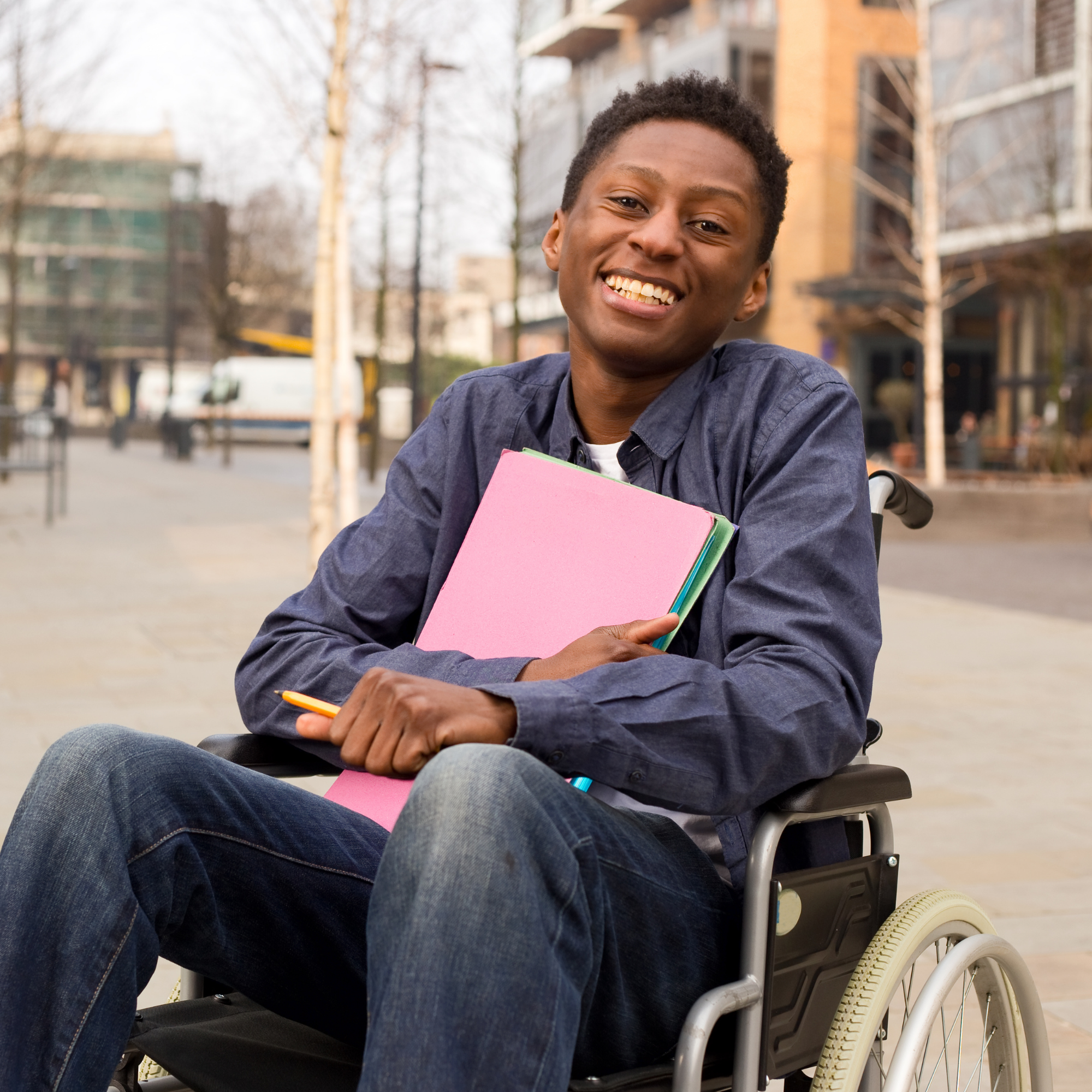 Young man in wheelchair holding school books